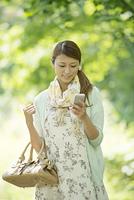 新緑の中でスマートフォンを見る女性