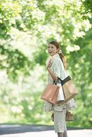 ショッピングバッグを持ち微笑む女性