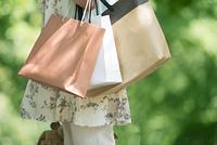 ショッピングバッグを持つ女性の手元