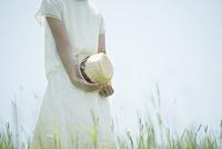 草原で帽子を持つ女性の手元