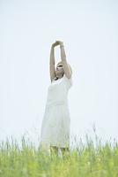 草原で伸びをする女性