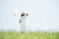 草原で風船を持つ女性の後姿