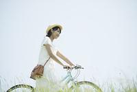 草原で自転車を押す女性