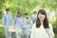 新緑の中で微笑む大学生