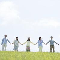 草原で手をつなぐ大学生