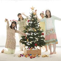 クリスマスツリーの飾り付けをする4人の女性