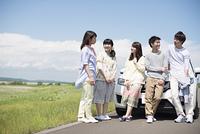 車の周りで談笑をする大学生