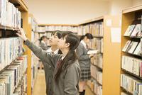 図書室で本を選ぶ女子学生