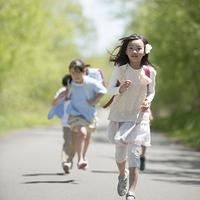 一本道を走る小学生