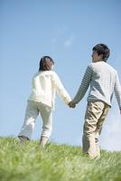 草原で手をつなぐカップルの後姿