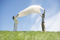 草原で布を広げるカップル