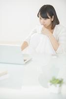 コーヒーカップを持ちパソコン操作をする女性