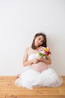 花束を持つドレスを着た妊婦さん