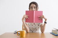 本で顔を隠す女性