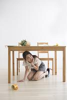 地震でテーブル下に避難する女性