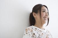 笑顔で壁にもたれる女性