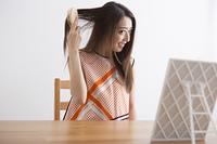 部屋で髪をブラッシングする女性