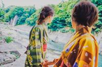 温泉旅館付近の河原を散策する浴衣の日本人女性