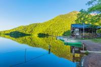 早朝の湯ノ湖と新緑の山並