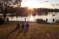 夕暮れ時の湖畔でくつろぐ人々