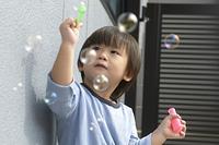シャボン玉と戯れている三歳の男の子