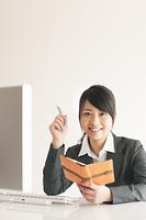 スケジュール帳を持ち微笑むビジネスウーマン