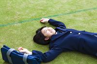 グラウンドの芝生に寝転がる女子高生