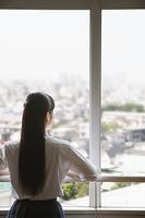 教室の窓から街並みを見る女子高生