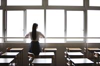 教室の窓から外を眺める女子高生