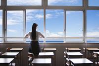 教室の窓から海を眺める女子高生