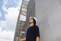 上を見上げる大工