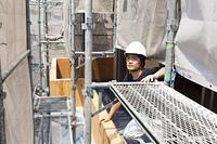 足場から上を見上げる大工
