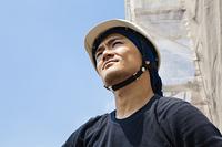 足場から空を見上げる大工