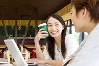 カフェでパソコンを見る大学生の男女