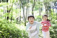 山の中を走る男の子と女の子