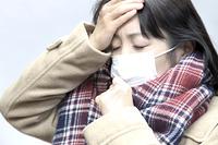 手を息で暖める女性