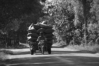 国道を走る積載オーバーの三輪車