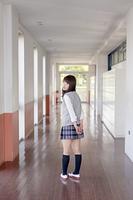 学校の廊下で振り返る女子高生
