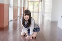 学校の廊下に座る女子高生