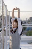 学校の屋上で伸びをする女子高生