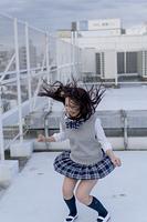 学校の屋上でジャンプをする女子高生