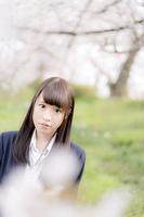 桜の下でたたずむ女子高生