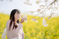 桜と菜の花の間に立つ女性