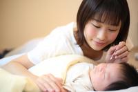 赤ちゃんの耳掃除をする母親