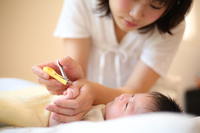 赤ちゃんの爪を切る母親
