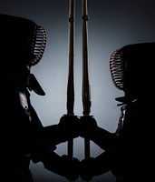 Two dark kendo fighters opposite each other