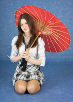 Beautiful girl sits with the Japanese umbrella
