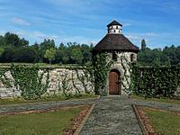 Burgmauer mit Turm und Tor von Efeu bewachsen