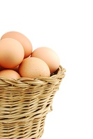 Close-up of eggs in a wicker basket on white