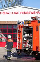 Feuerwehrmann vor Einsatzfahrzeug